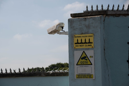 A CCTV security camera and warning signs protecting a property