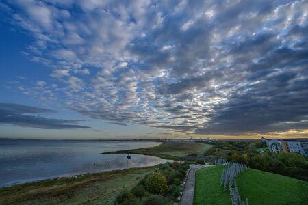 Scudding cumulus clouds race across an estuary causing high pressure weather 写真素材