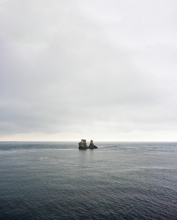 huge rock and island in the sea Imagens