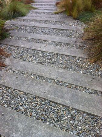 A landscaped sleeper and stone coastal walkway Stock Photo
