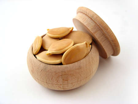 Pumpkin seed in wooden pot over white. Stock Photo