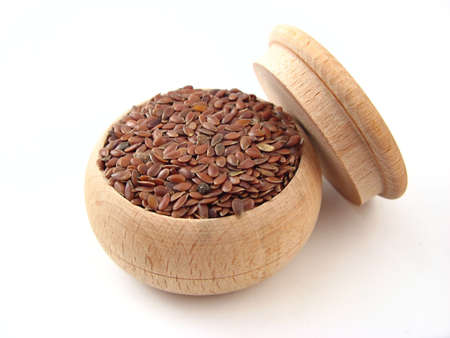Linseed in wooden pot over white.