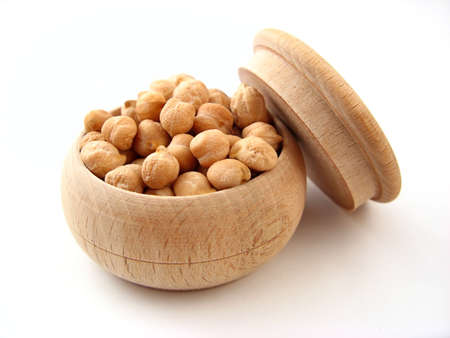 Chickpea in wooden pot over white.