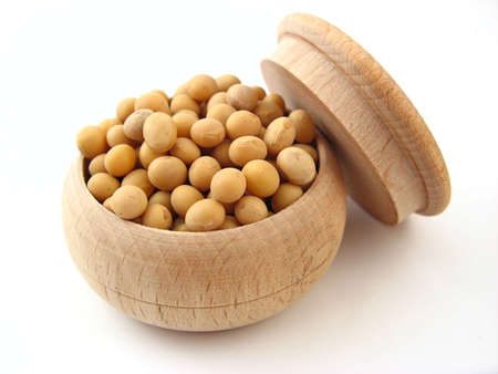Soybean in wooden pot over white. Stock Photo