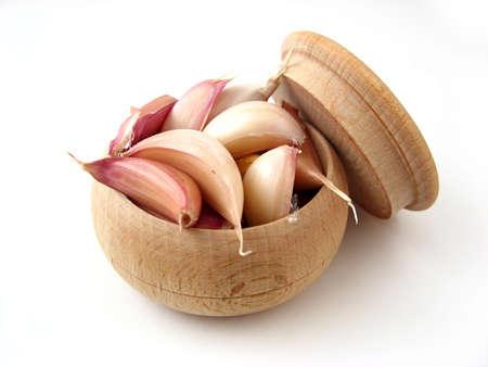 Garlic in wooden pot over white.