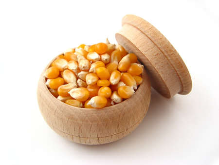 Corn in wooden pot over white.