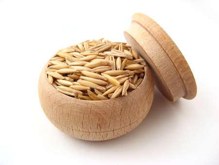 Oat in wooden pot over white.