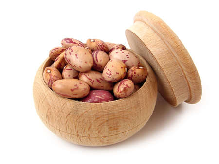 Pinto beans in wooden pot over white. Stock Photo
