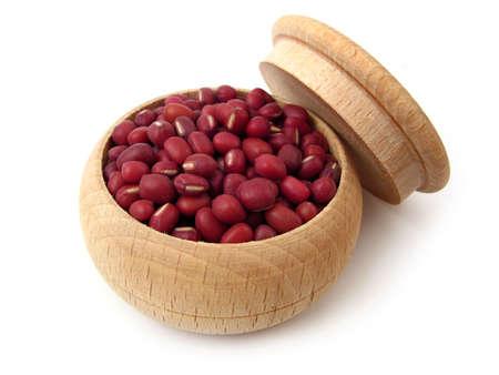 Azuki bonen (rode bonen) in houten pot over wit.