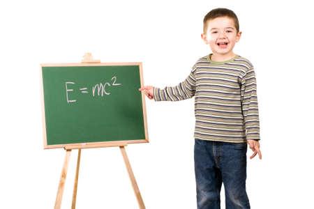 Boy writing Einsteins equation on chalkboard Stock Photo