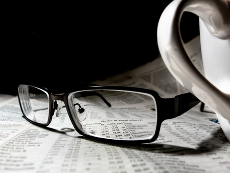 Newspaper with reading glasses and coffee cup