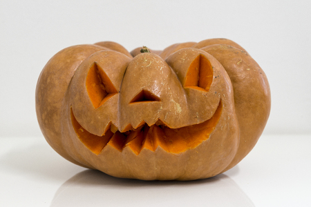 orange halloween pumpkin with carving, crushed and collapsible typology, on a background in nature or white Stock fotó