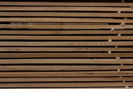 Background of a stack of wooden boards on storage lying horizontally
