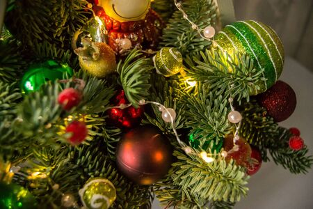 Christmas composition of fir branches with Christmas decorations and garlands.