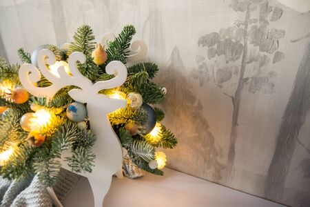 Christmas composition of fir branches with Christmas decorations and garlands on a winter background.