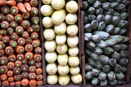 agriculture sri lanka: A display of carrots, white aubergines and green bananas for sale at a Sri Lankan market.