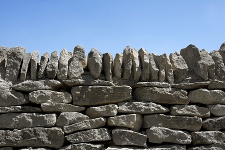 dry stone: A dry stone wall against clear blue sky. Space for text.