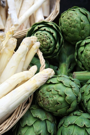 Baskets of asparagus and fresh artichokes for sale at a market photo