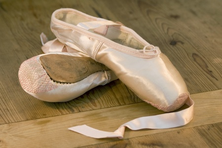 pointe: A pair of discarded ballet shoes on wooden dance studio floor
