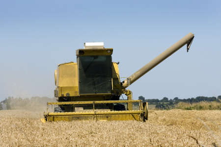 Combine harvester preparing to offload the harvested wheat  Stock Photo