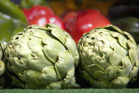 pimiento: A close up of artichokes with colourful mixed peppers in the background Stock Photo