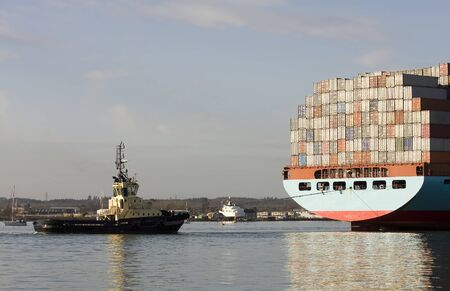 tug boat: Container ship being brought into port by tug boats, Southampton, England