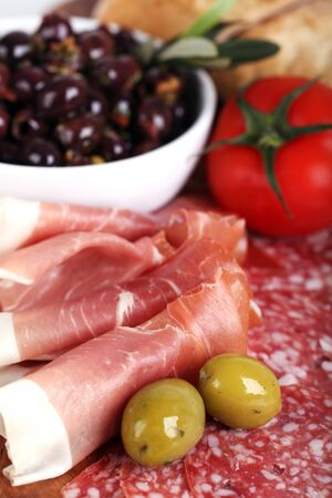 A platter of cold meats, olives, tomato and bread rolls. Tapas style assortment. Intentional shallow depth of field. photo