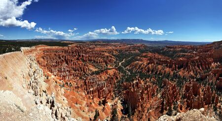 hoodoo: A panorama of the Hoodoo rock spires of Bryce Canyon, Utah, USA, with blue sky and fluffy clouds.
