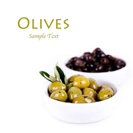 Green and black olives in a white ceramic bowl with olive branch. Isolated on white with space for text. photo