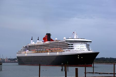 dockside: SOUTHAMPTON, UK - 5 JUNE: Cunard ship Queen Mary 2 sails in at dawn to meet Queen Elizabeth & Queen Victoria in the port of Southampton for the first time to celebrate the Diamond Jubilee. 5 JUNE 2012