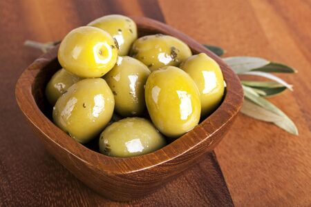 Green olives in a wooden bowl with olive branch, on wooden background.  photo