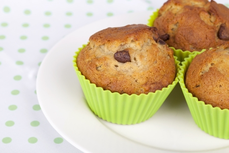 Banana Chocolate chip muffins on white plate with green and white spotted tablecloth  photo