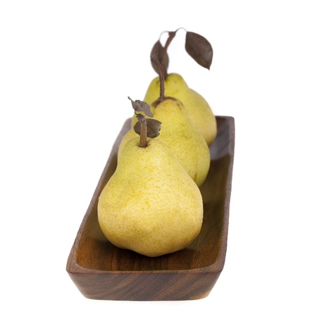 Three green pears in wooden bowl  Isolated with Intentional shallow depth of field  Stock Photo - 15487123