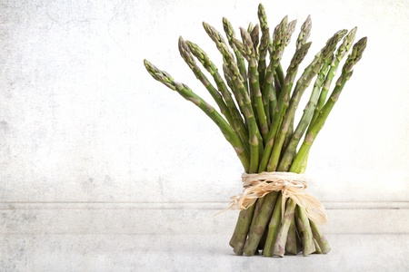 A bundle of fresh asparagus spear, tied with rafia against vintage effect background photo