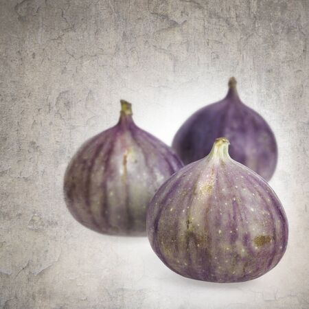 Three fresh figs with vintage effect background photo