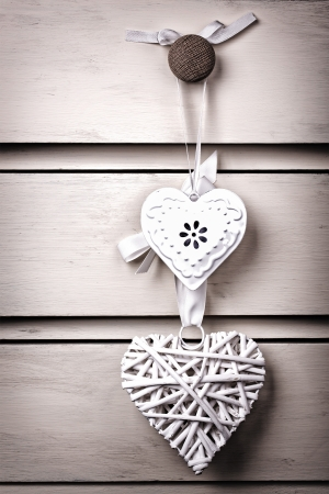 intentional: A wicker and a tin heart hanging from the knob of a chest of drawers. Vintage effect with intentional vignette. Stock Photo