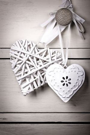A wicker and a tin heart hanging from the knob of a chest of drawers. Vintage effect with intentional vignette. Stock Photo - 17117297
