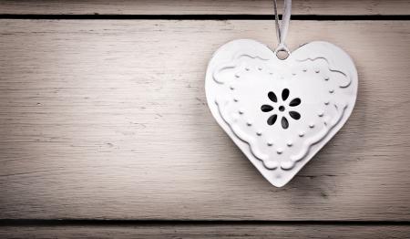 шик: Старинные сердца олова висит на ленте, с Старые деревянные фон и преднамеренные виньетка. Место для вашего текста