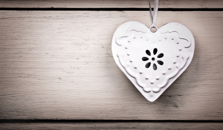A vintage tin heart hanging from a ribbon, with old wood background and intentional vignette. Space for your text