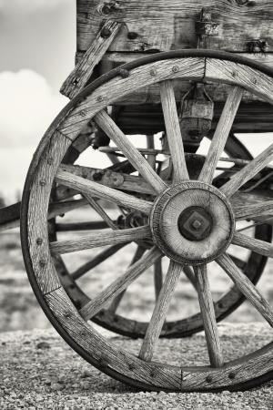 carreta madera: Detalle de las ruedas de un carro viejo, Utah, EE.UU.. Blanco y negro con tono sepia leve.