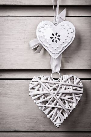 A wicker and a tin heart hanging from the knob of a chest of drawers. Vintage effect with intentional vignette. Stock Photo - 17217272