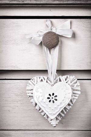 A wicker and a tin heart hanging from the knob of a chest of drawers. Vintage effect with intentional vignette. Stock Photo - 17217262