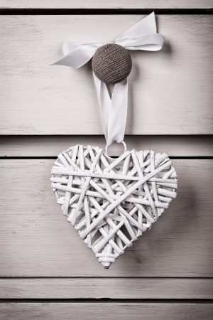 A wicker and a tin heart hanging from the knob of a chest of drawers. Vintage effect with intentional vignette. photo