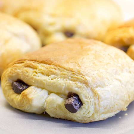 boulangerie: A closeup of Pain au Chocolat baking on a non-stick oven tray  Intentional shallow depth of field   Stock Photo