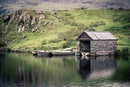 quaint: An old stone boathouse on a lake in Snowdonia, North Wales  Nostalgic effect with intentional vignetting  Editorial