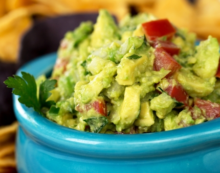A bowl of fresh guacamole with corn tortilla chips  Intentional shallow depth of field