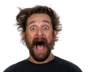 Goofy young man, with full beard and moustache and wild hair style, screams with joy Stock Photo