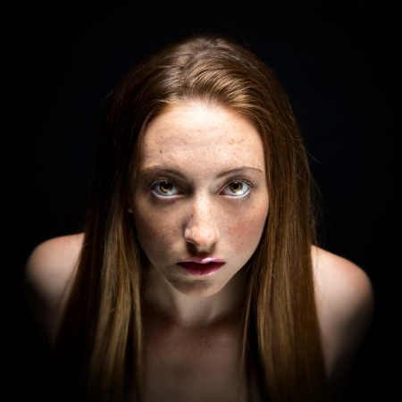 auburn: Low key portrait of a young, fresh faced woman.