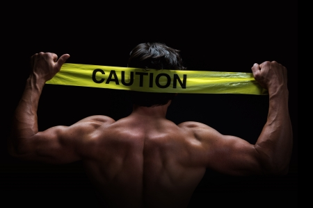 Attractive young man flexes his muscles whilst holding a caution tape behind his head photo