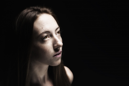 Low key portrait of young woman on black background, looking up into the darkness   Stock Photo
